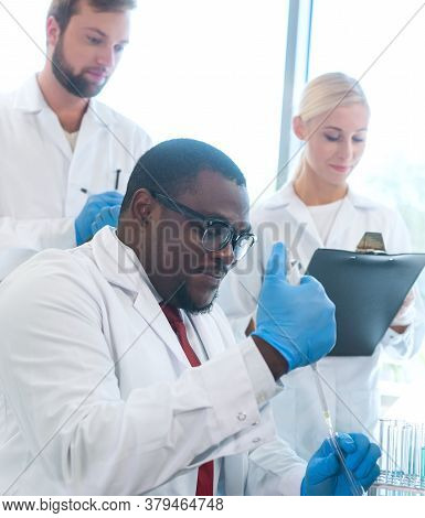 Scientist And Students Working In Lab. Doctor Teaching Interns To Make Blood Analyzing Research. Bio