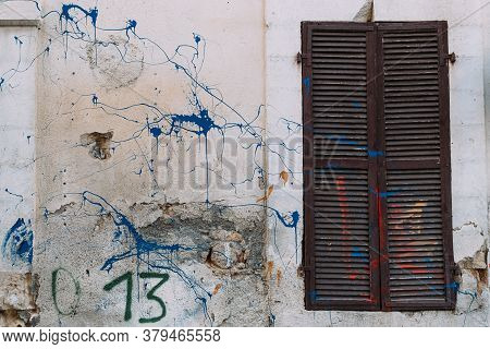 Closed Wooden Brown Shutters On Grungy Textured Wall. Splashes Of Blue And Red Paint On Wall. Old Cl