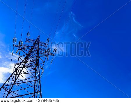 High Voltage Post Or Power Transmission Tower Agains Blue Sky. Silhouette Of Electricity Post And Hi