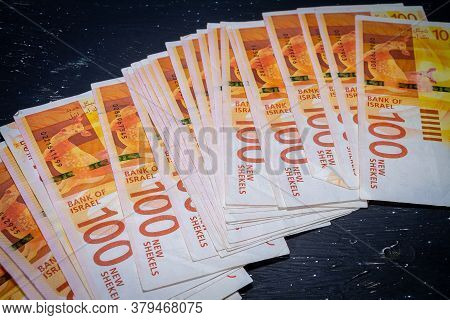 Banknotes Of 100 New Israeli Shekels Lie On A Black Background.