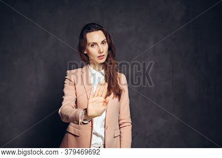 Adult Caucasian Woman Show Stop Sign On Grey Dark Background With Copy Space