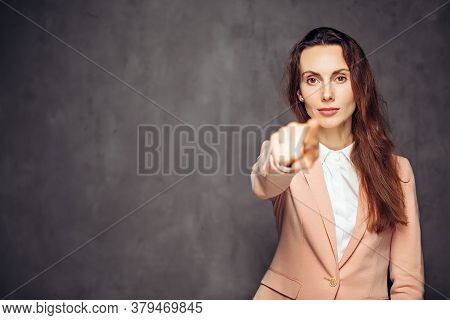 Adult Caucasian Woman Point With Finger On Grey Dark Background With Copy Space