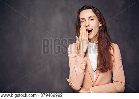 Adult Caucasian Woman Yawning On Grey Dark Background With Copy Space