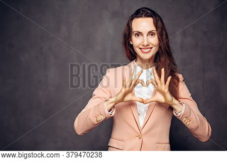 Adult Caucasian Woman Show Heart Sign On Grey Dark Background With Copy Space