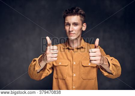 Young Caucasian Man Show Thumbs Up On Grey Dark Background With Copy Space