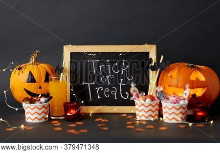 halloween and holiday decorations concept - chalkboard with trick or treat lettering, jack-o-lanterns or carved pumpkins, candies, burning candles and glass of juice with paper straw