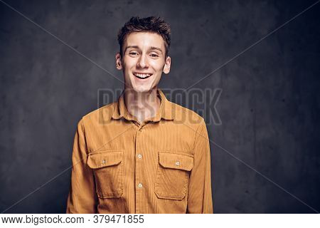 Happy Young Caucasian Man On Grey Dark Background With Copy Space