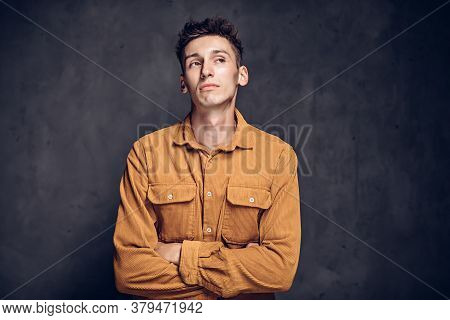Pensive Young Caucasian Man On Grey Dark Background With Copy Space