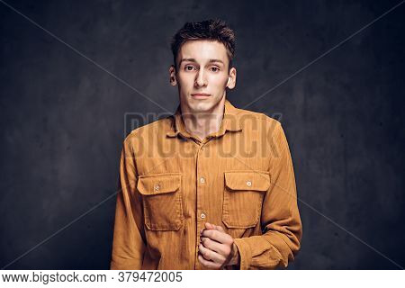 Frightened Young Caucasian Man On Grey Dark Background With Copy Space