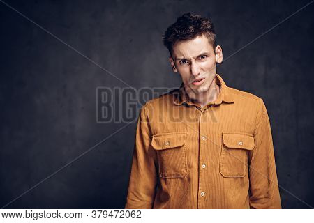 Dissatisfied Young Caucasian Man On Grey Dark Background With Copy Space