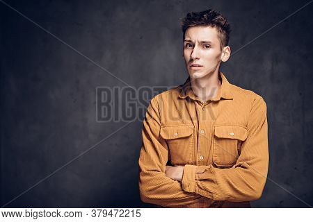 Displeased Young Caucasian Man On Grey Dark Background With Copy Space