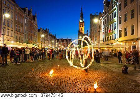 Gdansk, Poland - July 17, 2020: Fire dance at the Long Market in Gda?sk at dusk, Poland