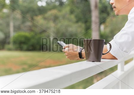 Man Using Mobile Phone With Coffee Mug On Balcony In Garden View