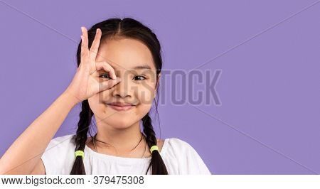 Okay. Asian Little Girl Covering Eye With Ok Sign Looking At Camera Posing In Studio On Purple Backg