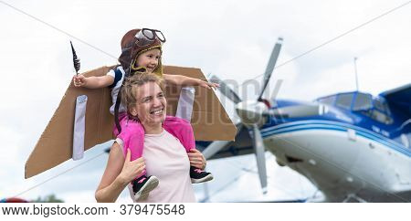 A Loving Caucasian Woman Is Playing With Her Little Daughter In Airplanes At The Airfield. A Little