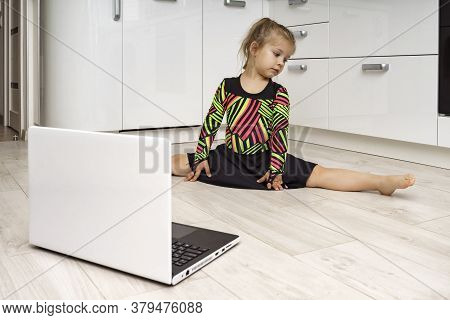 Little Girl In A Gymnastic Leotard Is Engaged In Online Gymnastics At Home And Looks At A Laptop. Si