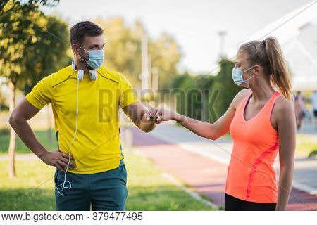 Young Couple Is Getting Ready For Outdoor Workout With Protective Masks. Covid-19 Responsible Behavi