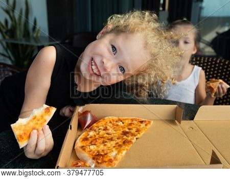 Funny kids eating pizza at home