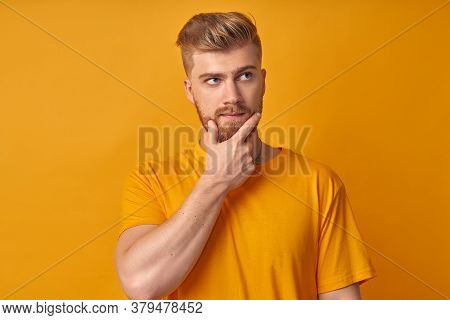 Pensive Guy With A Sly Look Holds His Hand On His Chin And Looks Away. Young Sexy Hipster On A Yello