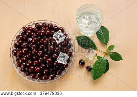 Ripe Cherries In A Glass Dish In Drops Of Water And A Drink With Ice Cubes In A Glass. Green Branch
