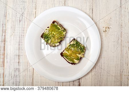 Slice Of Cereal Bread With Cream Cheese And Avocado On A White Plate. Vegetarian Sandwich.
