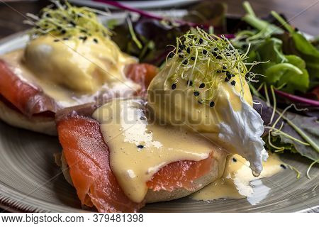 Delicious Breakfast Or Brunch, Egg Benedict With Smoked Salmon, And Green Lettuce