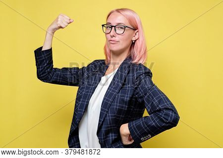 Young Woman In Suit Shows Her Muscles, Strength And Power Concept