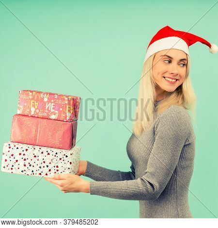 A Beautiful Sexy Girl In A New Year's Hat And Gray Dress, Hold In Hands Gifts Celebration Of Christm