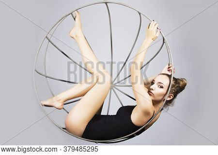 Young Woman In A Black Swimsuit On A Metal Cage On A White Background