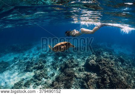 Woman With Fins Swimming Underwater With Big Sea Turtle.