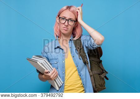 Puzzled Student With Books Scratching Her Head Trying To Make A Decision.