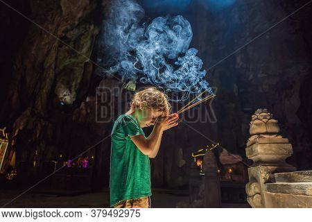 Young Boy Praying In A Buddhist Temple Holding Incense Huyen Khong Cave With Shrines, Marble Mountai