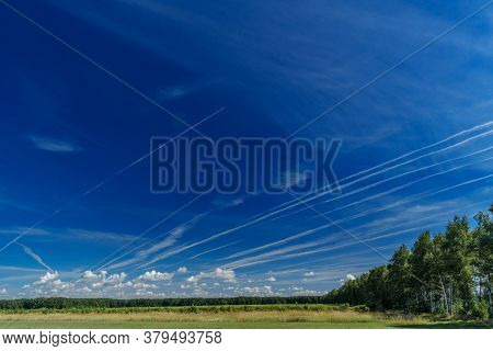 White Jet Passenger Plane Flying At High Altitude In The Blue Sky. White Traces Of Condensation Of W