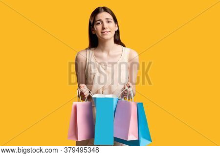 Disappointed Shopper. Online Shopping. Sad Woman With Paper Bags Isolated On Orange. Dislike Purchas