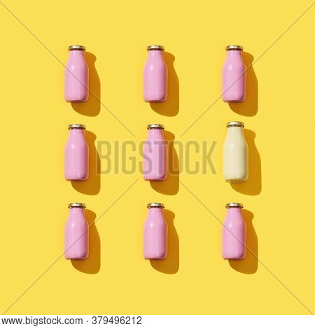 Creative Pattern With Small Glass Bottles For Juice Or Yogurt. Packaging Template Mock Up On Yellow