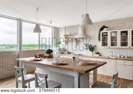 Side View Of Modern Kitchen At Home With White Interior, Tableware On Dining Table, Cooking Hood Ove