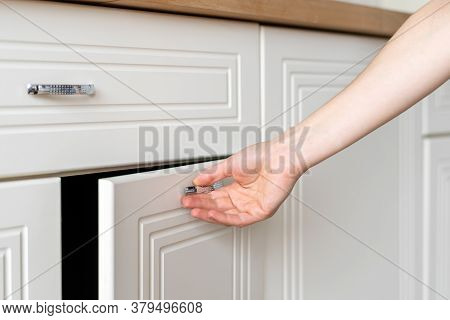 Cropped View Of Woman Hand Open Door At Cupboard Furniture Standing On Modern Kitchen At Home With W