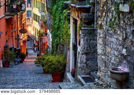 Bellagio, lake Como, Milan, Italy. Famous stone stairs street. Evening Nighttime with blue sky and lights of outdoor lanterns. Picturesque italian architecture of famous luxury Alpine health resort.
