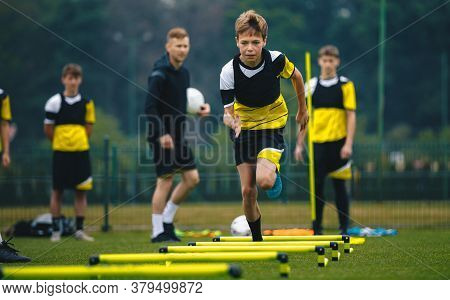 Boys On Football Training Session With Two Young Coaches. Junior Level Soccer Player Running And Doi