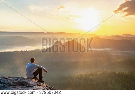 Alone Hiker Man Sitting On A Rock And Enjoying Spectacular View. Pure Nature