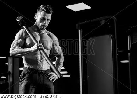 Front View Of Muscular Man Holding Big Sledgehammer On Shoulder. Monochrome Portrait Of Shirtless Ca