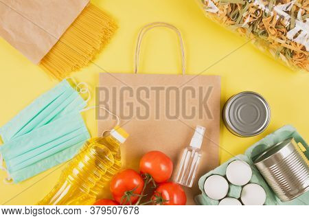 Food And Medicaments Donations With Paper Bag On Yellow Background With Copyspace - Pasta, Fresh Veg