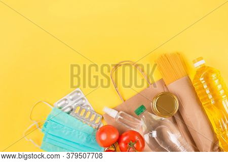Closeup Of Food And Medicaments Donations With Paper Bag On Yellow Background With Copyspace - Pasta