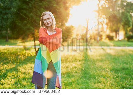 Young Caucasian Tolerant Woman In Casual Outfit Posing In Park, Enjoying Summer Sunset On Background