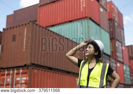 Young Asian Woman In Safety Uniform  Is Looking At Copy Space For Your Putting Text At The Container