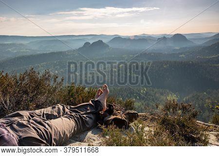 Tourist Sit On Peak Of Sandstone Rock  Lone Man Sit. Fall Mountain Mist. Tourist Sitting On The Edge