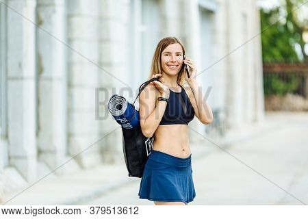 Young Athletic Woman With Water Phone And Sports Mat Doing Sport Outside In Bright Sports Suit.