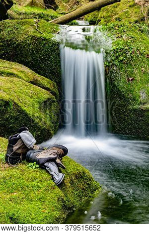Discoverer  Boots And Socks On Mossy Stone And Relaxing During Trip In Nature