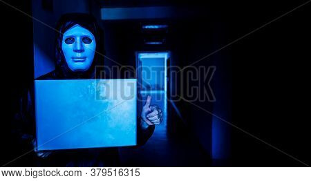 Anonymous Computer Hacker In White Mask And Hoodie. Obscured Dark Face Holds A Laptop Tight In His H