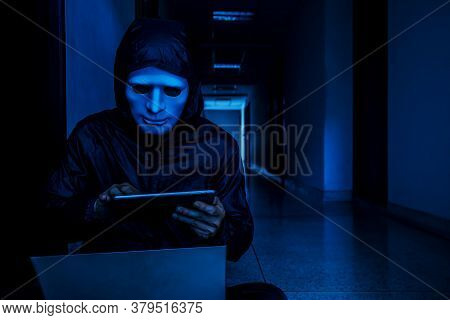 Anonymous Computer Hacker In White Mask And Hoodie. Obscured Dark Face Working On Her Labtop And Tab